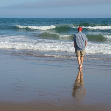 man walking on beach, reflection in sand, waves, Lawrencetown Beach